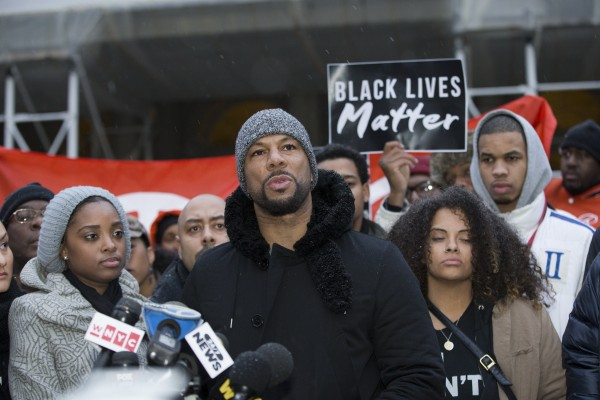 Common speaking as the Justice League held a press conference featuring rap artists and activists on the City Hall steps, wednesday, concerning police brutality and racial disparities in policing. Left, Tamika Mallory; Right, Cherrell Brown, National Organizer, Equal Justice USA, rear right Eric Garner Jr. photo William Farrington